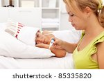 Sad girl with temperature laying sick in bed - her mom beside - stock photo