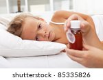 Sick girl waiting for her medication laying in bed - stock photo