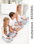 Happy healthy life concept with family doing relaxation exercise at home - stock photo