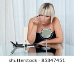 attractive woman putting make up at her home - stock photo
