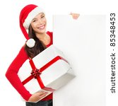Beautiful christmas woman in santa hat holding empty board sign isolated on white background. - stock photo
