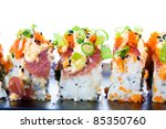 A colorful spicy Ahi tuna roll with raw seafood, fish eggs, avocado, rice and more.  Delicious Asian cuisine. - stock photo