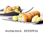 Two plates of Asian seafood sushi rolls with pickled ginger and wasabi. - stock photo