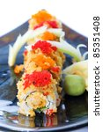 Red and orange fish eggs or tobiko on crunchy seafood sushi rolls at an Asian food restaurant. - stock photo