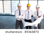 Business people with a plan on the construction site - stock photo