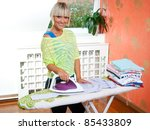attractive woman ironing in her home - stock photo