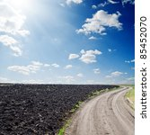 rural road near black ploughed field - stock photo