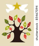 Christmas tree with pace doves holding and shiny golden star on top. - stock photo
