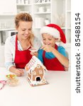 Final touches on the gingerbread house - people at christmas time in the kitchen - stock photo