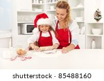 Happy woman and girl stretching the christmas cookie dough together - stock photo