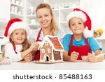 Happy christmas family in the kitchen decorating a gingerbread house - stock photo