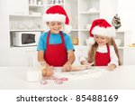 Happy christmas kids in the kitchen stretching the cookie dough - stock photo