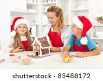 Family having fun in the kitchen while decorating a gingerbread cookie house - stock photo