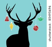 Christmas reindeer silhouette with decorations hanged from its antlers. - stock photo