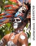 TULUM, MEXICO - JULY 15: Unidentified man in Mayan traditional ornamental feather headdress playing on drums to please the rain god Xipe Totec on July 15, 2011 in Tulum, Quintana Roo, Mexico - stock photo