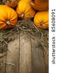 Orange Pumpkins Lay On A Woode...