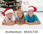 Happy kids at christmas time laying in front of the tree - stock photo