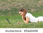 Young woman working in the park on laptop - stock photo
