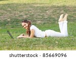 Young woman using laptop on the grass - stock photo