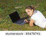Smiling young woman using laptop on grass - stock photo