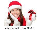 Santa girl holding christmas gift. Young happy woman in santa hat looking sideways showing Christmas present isolated on white background. Beautiful cute young santa woman. - stock photo
