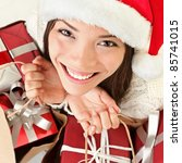 Christmas gifts santa woman shopping. Closeup portrait of young woman holding christmas presents in shopping bags. Beautiful smiling happy santa girl wearing santa hat. - stock photo