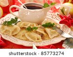 homemade  pierogi (ravioli) with mushroom and sauerkraut filling and clear red borscht (czerwony barszcz) for traditional polish christmas eve - stock photo