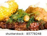 A beautiful plate filled with delicious food including a grilled steak topped with mushrooms and fresh dill, corn on the cob with melting butter and a baked potato. - stock photo