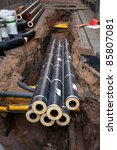 Dug up street with insulated metal pipes in a heap - stock photo