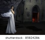 woman in white dress before a church - stock photo