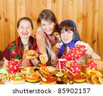 Women in traditional  clothes eating pancake with caviar during  Shrovetide - stock photo