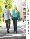Stock photo couple walking with dog in city street 85996510
