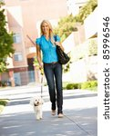 Stock photo woman walking with dog in city street 85996546