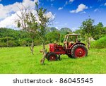 Old Red Tractor In A Green Field
