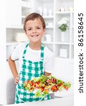 Happy boy wearing apron in the kitchen showing plate of vegetables on sticks - stock photo