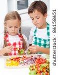 Kids preparing veggies on stick in the kitchen - healthy nutrition concept - stock photo