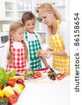 Woman and kids preparing a healthy meal together - stock photo