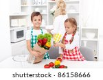 Kids with aprons unpacking groceries from paper bag in the kitchen - stock photo