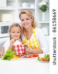 Woman and little girl preparing veggies on stick in the kitchen - stock photo