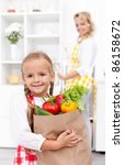 Happy little girl with the groceries bag in the kitchen - stock photo