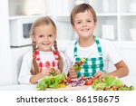 Happy healthy kids preparing a vegetables meal in the kitchen - stock photo
