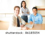 A caucasian man leads a business meeting with an Asian female and latino male - stock photo