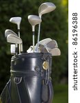A golf bag with three or four clubs in it including a driver,iron and putter - stock photo