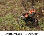 hunter in a wheelchair in the Autumn woods - stock photo