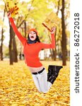 Girl with autumn leaf jump outdoor in park. - stock photo