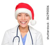 christmas doctor. Medical professional woman wearing red santa hat smiling at camera. Young Asian Caucasian woman isolated on white background. - stock photo