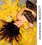 Brunette girl portrait lying in autumn leaves. - stock photo