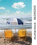 Two loungers under sun umbrella at the beach - stock photo