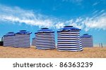 Blue and white striped tents on a beach in France - stock photo