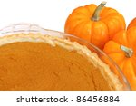 Thanksgiving pumpkin pie in a pie plate with pumpkins at side - stock photo